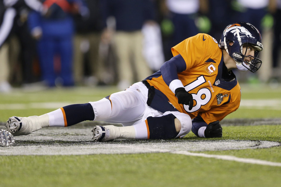 Photo - Denver Broncos' Peyton Manning lies on the ground after being tackled during the second half of the NFL Super Bowl XLVIII football game against the Seattle Seahawks Sunday, Feb. 2, 2014, in East Rutherford, N.J. (AP Photo/Julio Cortez)