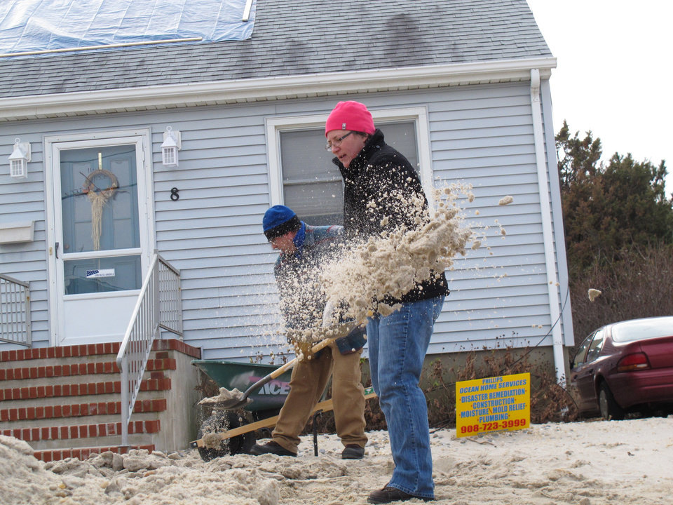 Photo - Susan VanVeen of Randolph, N.J. shovels sand from the front yard of a home near the ocean in Lavallette N.J. on Jan. 4, 2013, shortly before Congress voted to approve aid for victims of Superstorm Sandy. She was part of a group of volunteers who traveled to the shore to help storm victims. (AP Photo/Wayne Parry)
