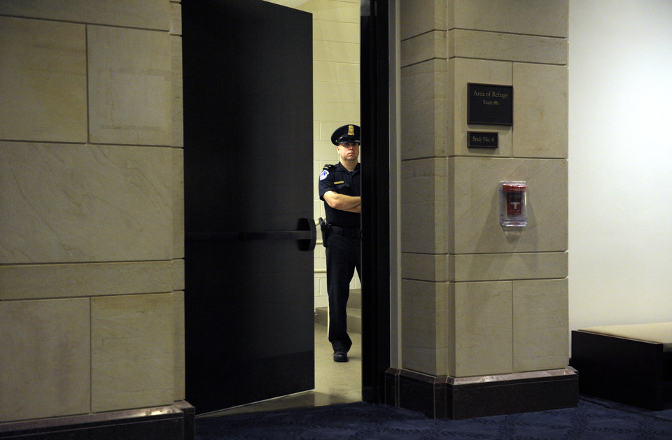 A Capitol Hill Police officer guards a staircase near the hearing room where former CIA Director David Petraeus is testifing before the House Intelligence committee on the Sept. 11, 2012 attack in Libya, on Capitol Hill in Washington, Friday, Nov. 16, 2012. (AP Photo/Cliff Owen)