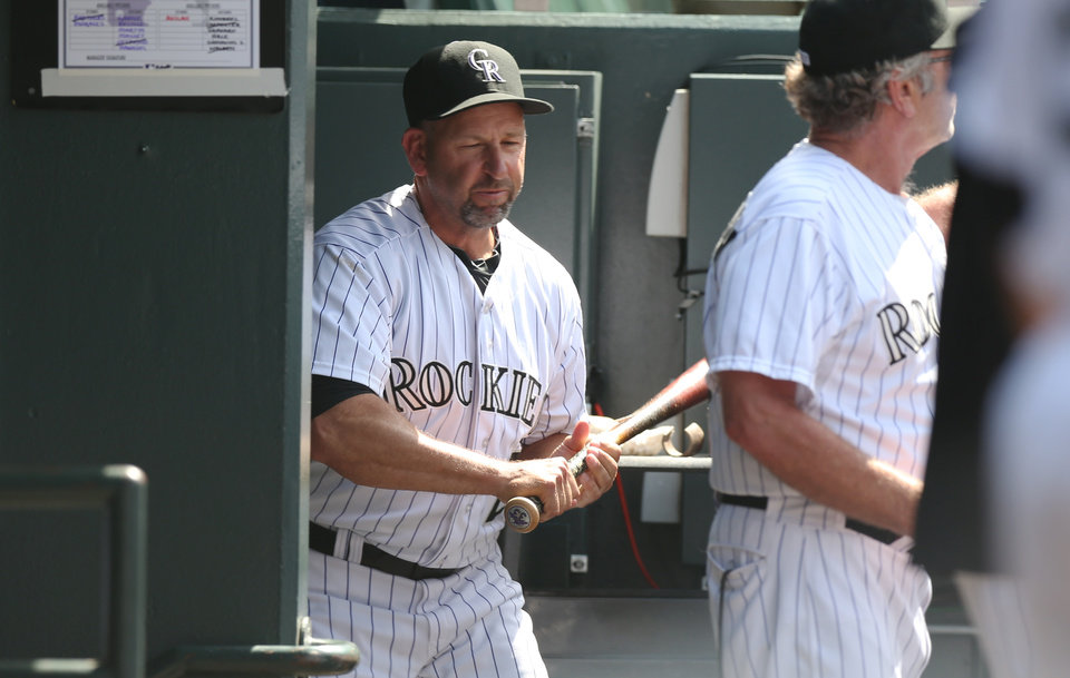 Photo - Upset over being ejected from the game, Colorado Rockies manager Walt Weiss grabs a bat on the way to smashing it against the wall in the team's dugout on the way to the showers against the Atlanta Braves in the eighth inning of the Rockies' 10-3 victory in a baseball game in Denver on Thursday, June 12, 2014. Weiss was ejected for arguing after the rockies' Corey Dickerson was hit by a pitch thrown by Braves relief pitcher David Carpenter. (AP Photo/David Zalubowski)