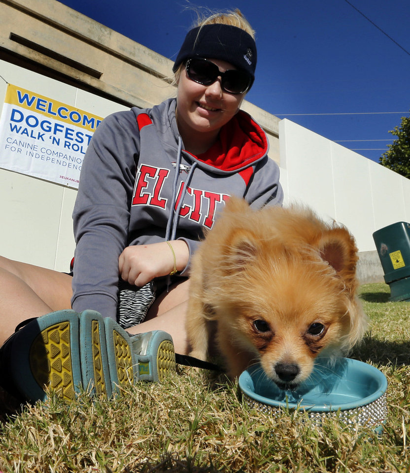 Photo - Tyiara Hall, of  Del City, gives her mini-pomeranian Izzy a drink after a one-mile walk during DogFest Walk 'n' Roll Oklahoma City to benefit Canine Companions on Saturday. PHOTO BY STEVE SISNEY, THE OKLAHOMAN  STEVE SISNEY - THE OKLAHOMAN