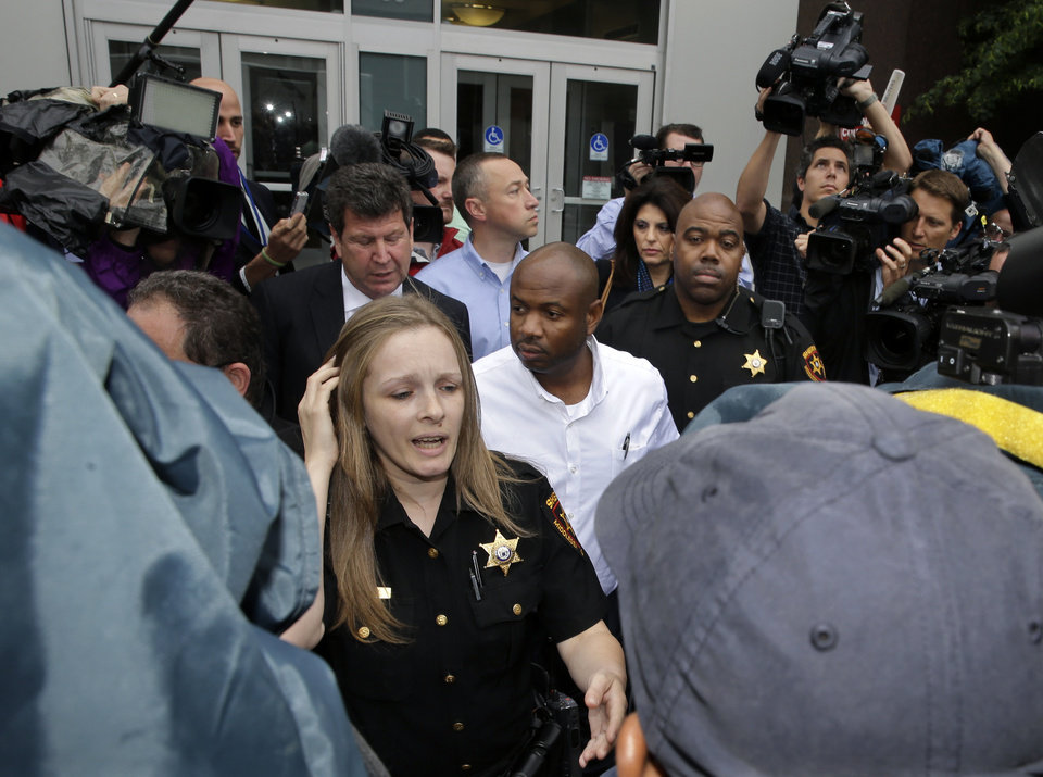 Photo - Kevin Roper, center, is led past cameras by Middlesex County Sheriff's officers as he leaves a court appearance Wednesday, June 11, 2014, in New Brunswick, N.J. Roper, a Wal-Mart truck driver from Georgia, was charged with death by auto and four counts of assault by auto in the wake of a deadly chain-reaction crash on the New Jersey Turnpike early Saturday, June 7, 2014, that killed comedian James McNair and left actor-comedian Tracy Morgan and two others critically injured.   (AP Photo/Mel Evans)