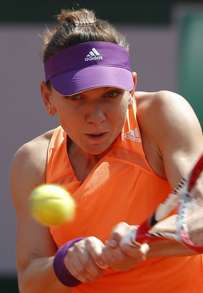 Photo - Romania's Simona Halep returns the ball to Russia's Maria Sharapova during their final match of  the French Open tennis tournament at the Roland Garros stadium, in Paris, France, Saturday, June 7, 2014. (AP Photo/Michel Euler)