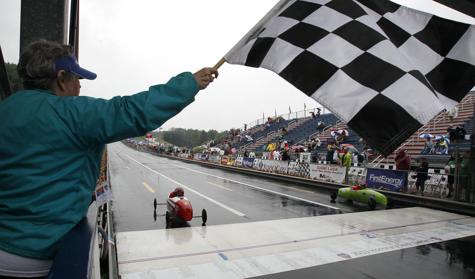 Janet Schroeter waves the checkered flag during one of the elimination heats in the 76th All-American Soap Box Derby, on Saturday, July 27, 2013, in Akron, Ohio. (AP Photo/Akron Beacon Journal, Paul Tople)