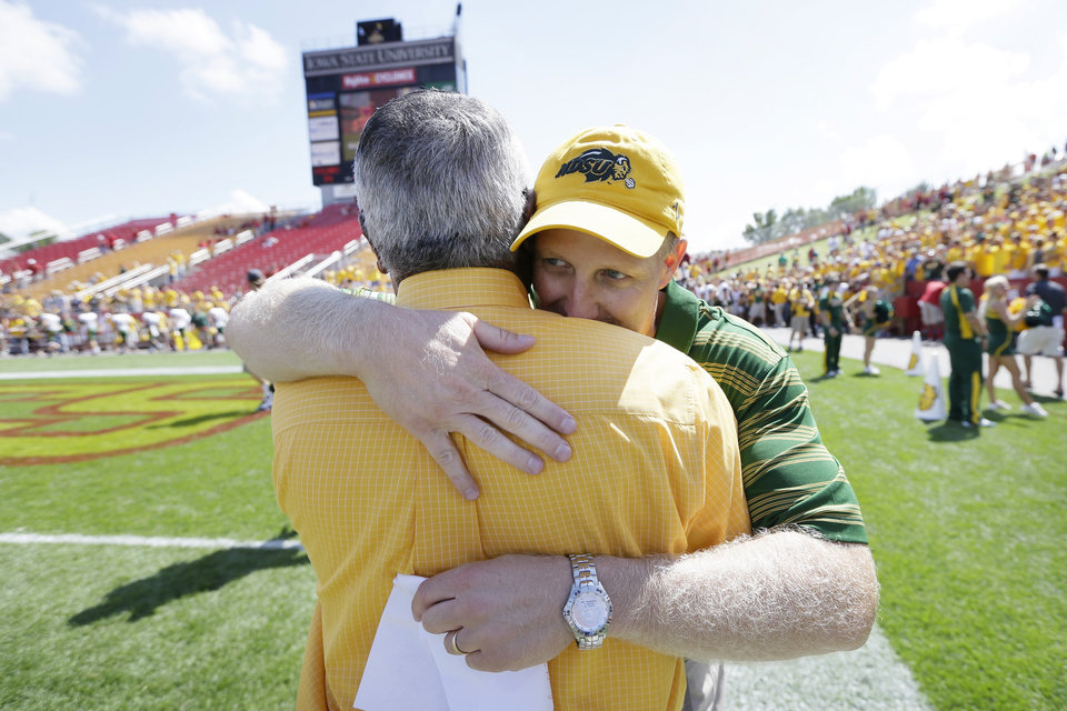 Photo - North Dakota State head coach Chris Klieman, right, gets a hug from North Dakota State athletic director Prakash Mathew after an NCAA college football game against Iowa State, Saturday, Aug. 30, 2014, in Ames, Iowa. North Dakota State won 34-14. (AP Photo/Charlie Neibergall)