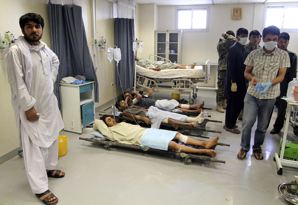 Photo -   Afghan victims of a suicide attack are seen on stretchers at a hospital in Kandahar, south of Kabul, Afghanistan, Wednesday, June 6, 2012. Two suicide bombers blew themselves up in a market area in southern Afghanistan on Wednesday, killing and wounding scores of people, authorities said. (AP Photo/Allauddin Khan)