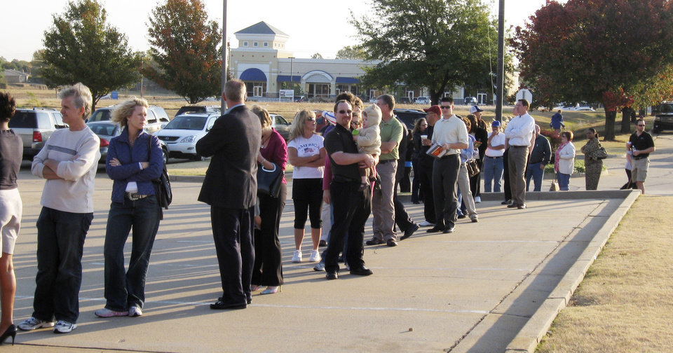 Photo - Voters line up this morning outside a polling place at the Edmond Public Schools Administrative Offices at Danforth and Kelly before 8 a.m. The lines stretched along the side of the building and into the parking lot. Photo by John Williams