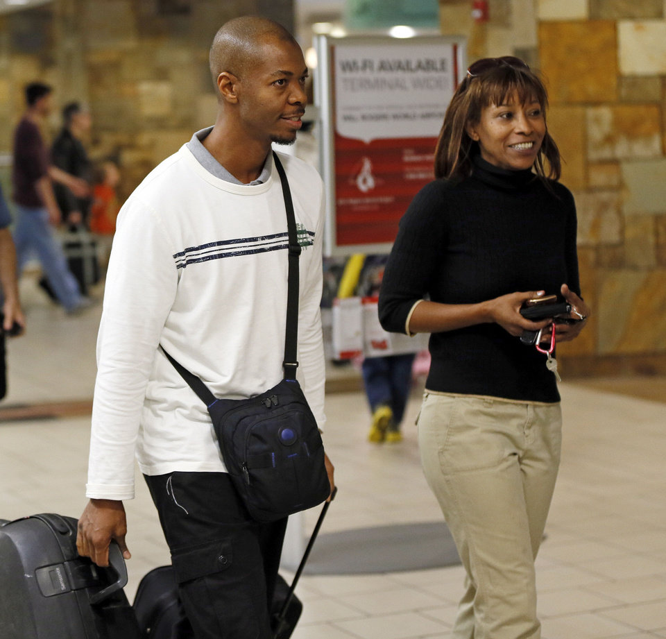 "Saadiq Long, left, walks with his sister, Ava Anderson, on Monday after arriving at Will Rogers World Airport in Oklahoma City. Long, an American Muslim living in Qatar, has been trying to return to Oklahoma since April and has been barred in his previous attempts because he is on a ""no-fly"" list.  Photos by Nate Billings, The Oklahoman"