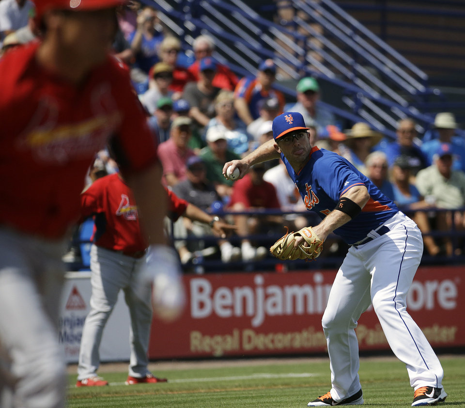Photo - New York Mets' David Wright throws to first base after fielding a sacrifice bunt by St. Louis Cardinals' Peter Bourjos, left, in the first inning of an exhibition spring training baseball game, Wednesday, March 12, 2014, in Port St. Lucie, Fla. (AP Photo/David Goldman)