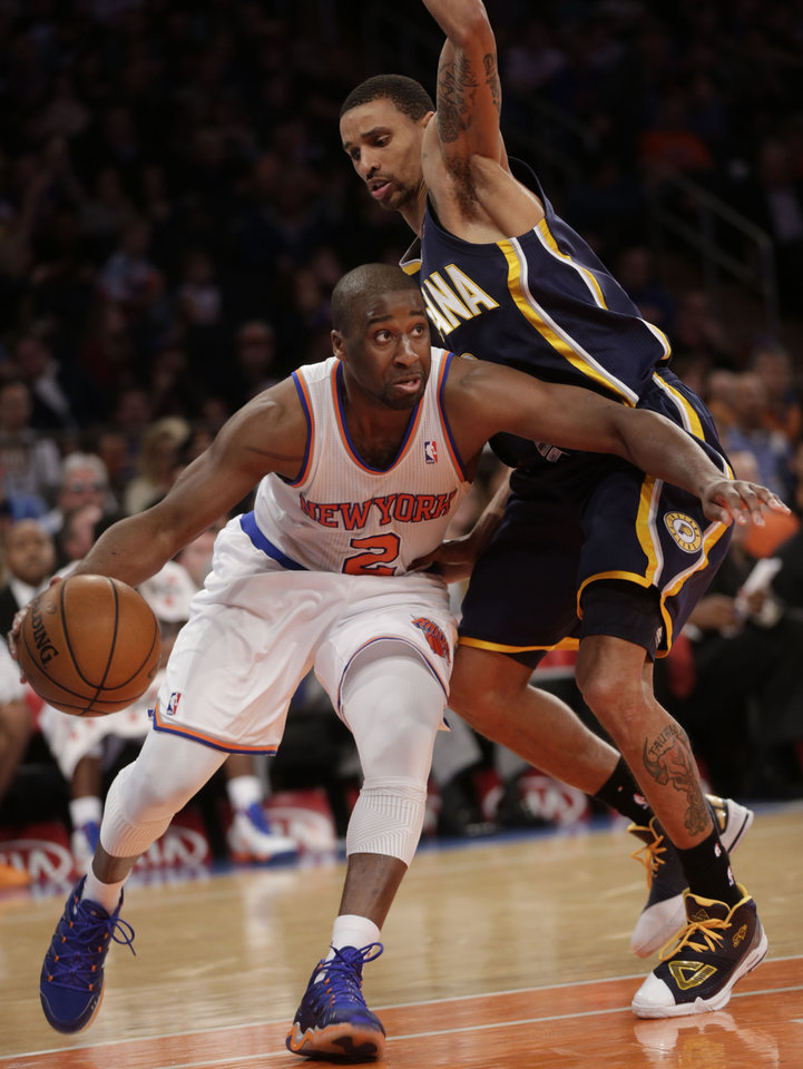 Photo - New York Knicks' Raymond Felton, left, drives past Indiana Pacers' George Hill during the second half of the NBA basketball game, Sunday, April 14, 2013, in New York. The Knicks won 90-80. (AP Photo/Seth Wenig)