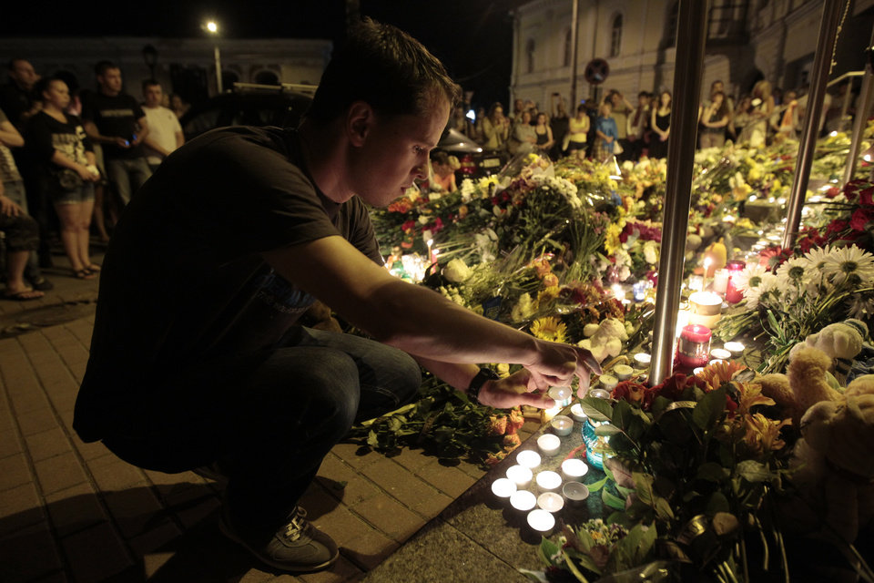 Photo - Man lights a candle near Dutch embassy to express condolences to air crash victims in Kiev,Ukraine, Thursday, July 17, 2014.  A Malaysian Airlines passenger jet  traveling from Amsterdam to Kuala Lumpur over Ukrainian airspace was shot down in eastern Ukraine on Thursday, and both the Ukrainian government and pro-Russian rebels blamed one another for the attack. (AP Photo/Sergei Chuzavkov)