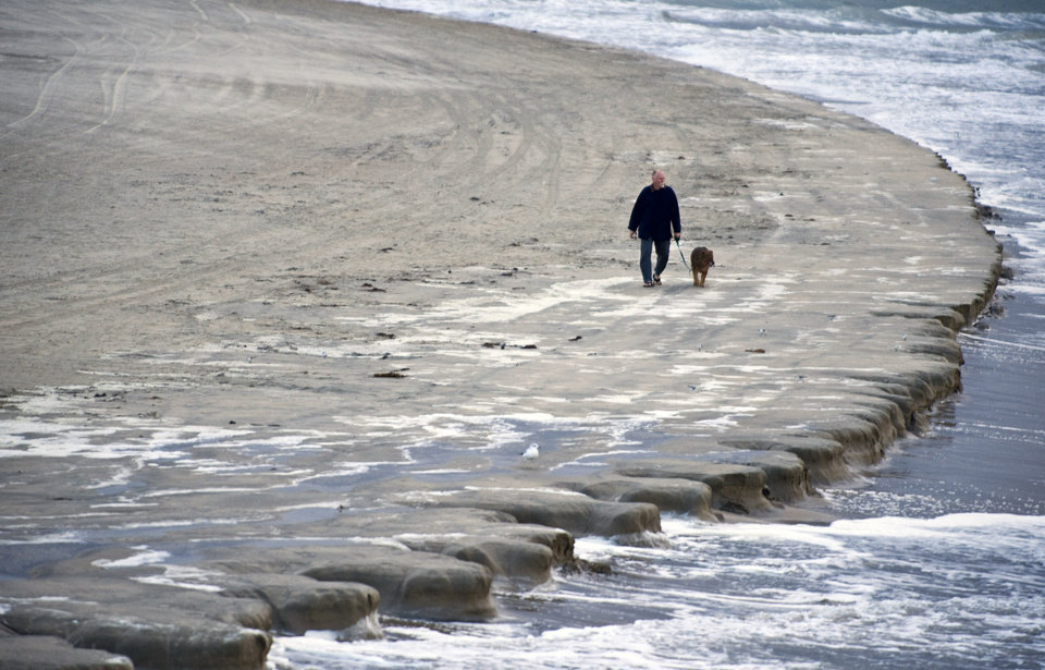 Photo - A man walks his dog along the beach early Thursday morning, Jan. 10, 2013 just south of the Newport Beach pier, as a king tide erodes the beach and strong winds and cold temperatures move into Orange County, Calif. King tide is a popular term used to refer to an especially high tide. (AP Photo/Orange County Register, Mark Rightmire) /// ADDITIONAL INFORMATION: 01/08/13 - Mark Rightmire, The Orange County Register