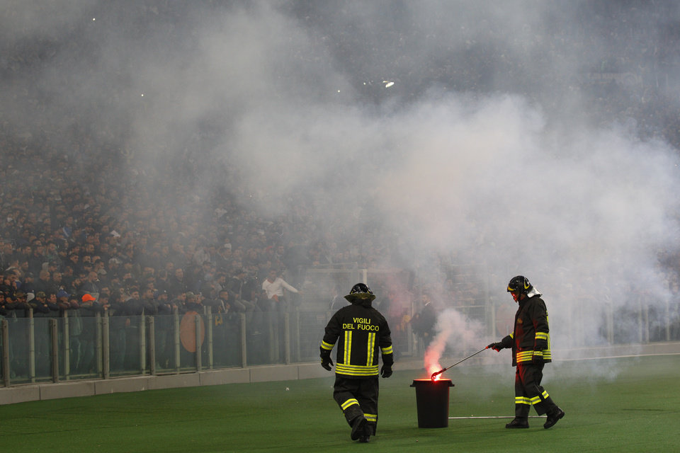Photo - Firefighters remove a flare prior to the start of Italian Cup final match between Fiorentina and Napoli in Rome's Olympic stadium Saturday, May 3, 2014. At least one fan and one police officer were reportedly shot before the Italian Cup final between Napoli and Fiorentina, and the fan was in serious condition. As a result, the start of the final was delayed, and there were scenes of violence inside the stadium with a firefighter injured by fireworks thrown from the stands. The shootings occurred in an area where Napoli fans were gathering for the match, the ANSA news agency reported. (AP Photo/Alessandra Tarantino)