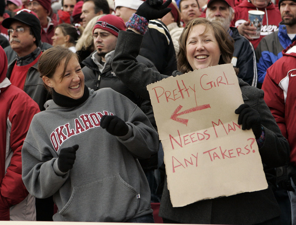 Photo - Melissa Goss-Jentz (right) tries to get on television to advertise her sister Jayme Goss, 23, during the college football game between the University of Oklahoma Sooners (OU) and the Oklahoma State University Cowboys (OSU) at the Gaylord Family-Memorial Stadium on Saturday, Nov. 24, 2007, in Norman, Okla. 