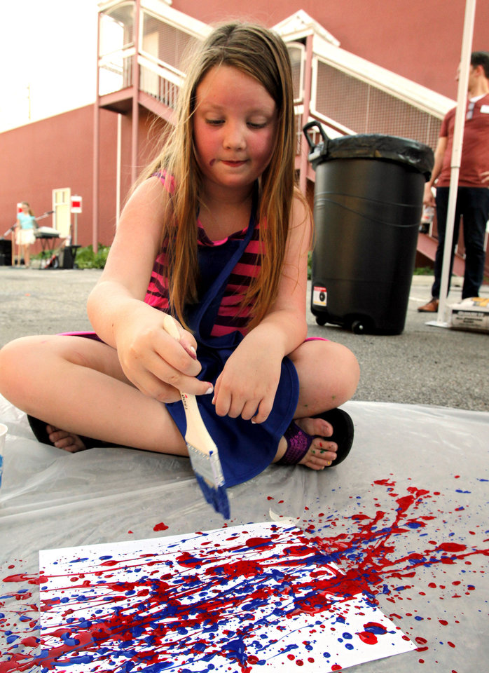 Above: Katie Elmore, 7, paints at the Kid's Corner.