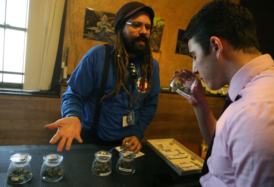 Photo - Customer Paxton Berlanga, of Indiana, right, smells a strain of marijuana, while being helped by employee Billy Archilla, inside the retail marijuana shop at 3D Cannabis Center, in Denver, Friday Feb. 14, 2014. The marijuana industry breathed a sigh of relief Friday after federal banking regulators issued long-awaited permission for them to access basic banking services. (AP Photo/Brennan Linsley)
