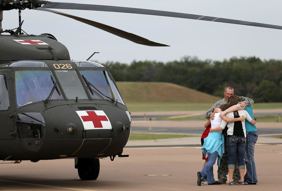 Staff Sgt. David Tillman says goodbye to his son, Patrick, daughters, Meagan, and Abby and wife Tiffany following an Oklahoma Aviation Command mobilization ceremony for Detachment 1, Company C, 2-149th General Support Aviation Battalion at the Army Aviation Support Facility in Lexington, Okla., Sunday, Sept. 16, 2012. The soldiers will receive additional training at Fort Hood before being deployed to Afghanistan. Photo by Sarah Phipps, The Oklahoman