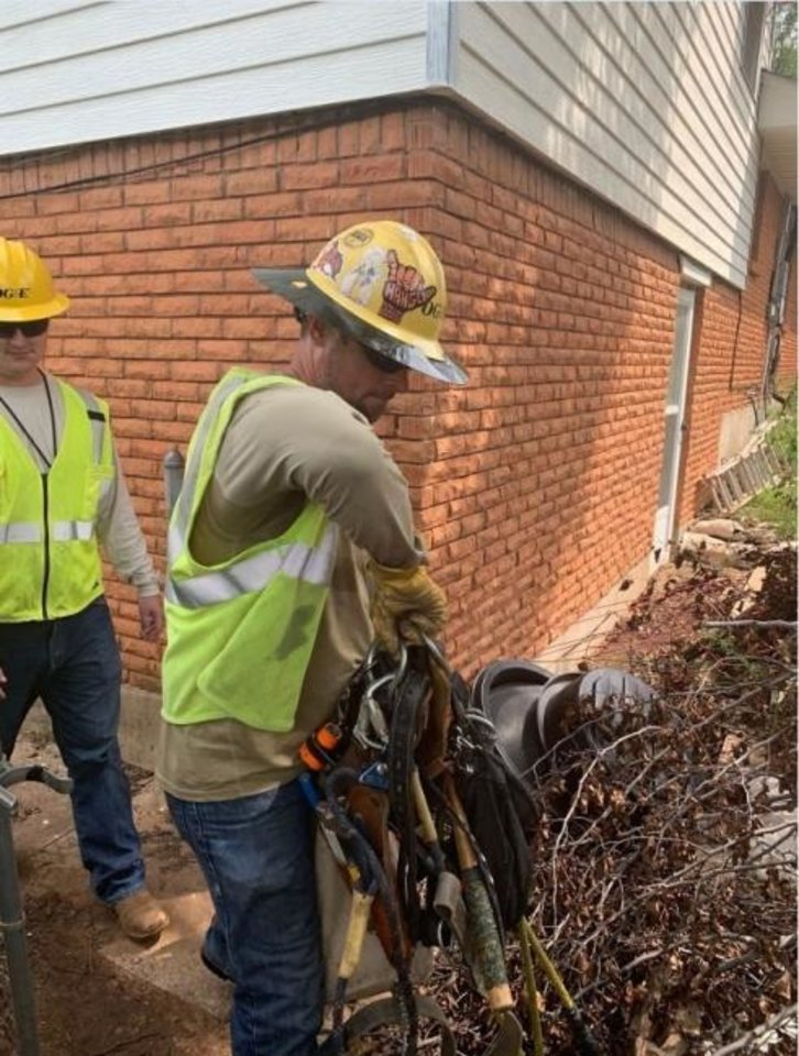 Photo -  Oklahoma Gas and Electric Co. linemen enter a yard at a home that was without power after severe storms on Aug. 26. Many lines carrying electricity from neighborhood distribution systems to homes were damaged by the storms.