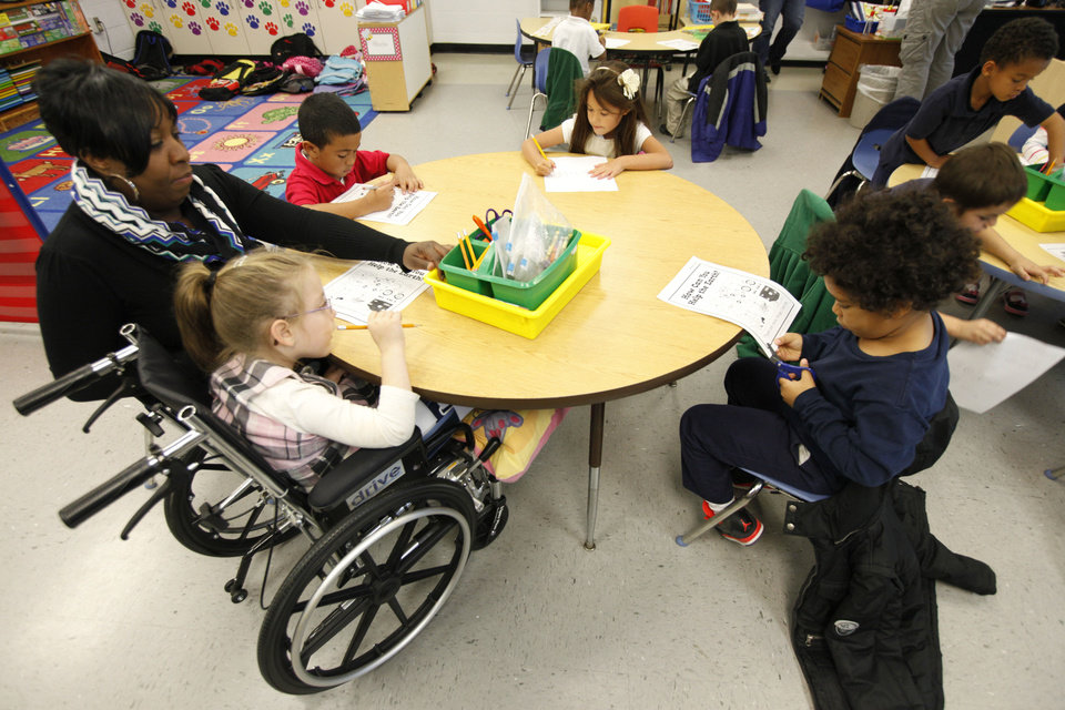 Photo - Special needs student McKiley Newlin, wheelchair, spends part of her day in mainstream classrooms at Johnson Elementary School. Photo by Paul Hellstern, The Oklahoman  PAUL HELLSTERN