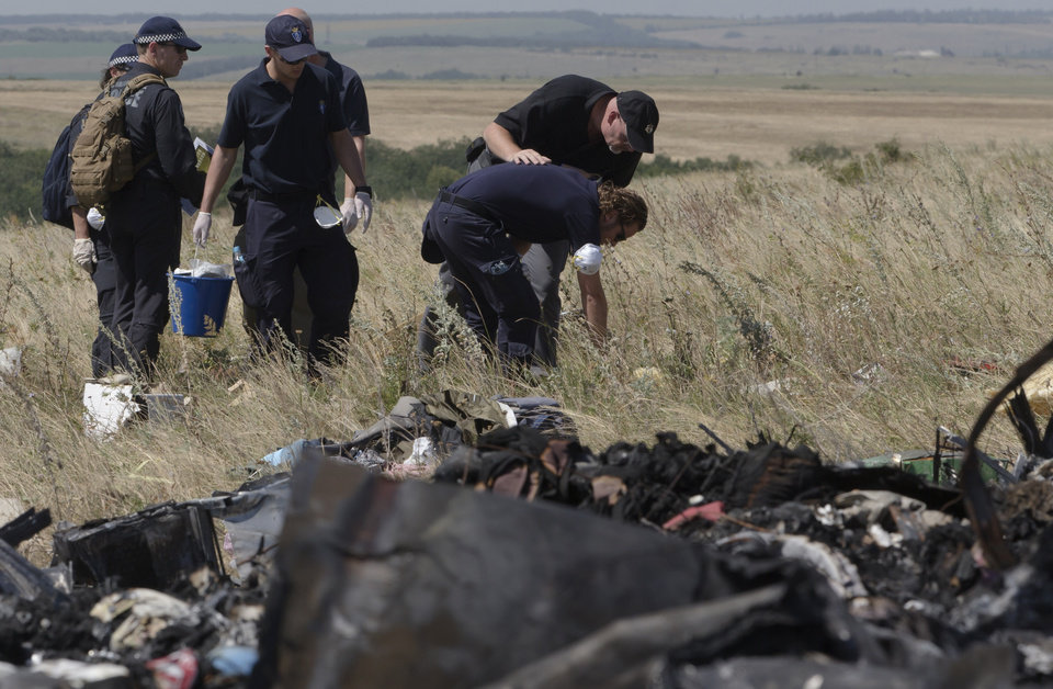 Photo - Australian and Dutch experts examine the area of the Malaysia Airlines Flight 17 plane crash in the village of Hrabove, Donetsk region, eastern Ukraine Friday, Aug. 1, 2014.  The investigators from the Netherlands and Australia plus officials with the Organization for Security and Cooperation in Europe traveled from the rebel-held city of Donetsk in 15 cars and a bus to the crash site outside the village of Hrabove. Then they started setting up a base to work from at a chicken farm. The investigative team's top priority is to recover human remains that have been rotting in midsummer heat of 90 degrees (32 degrees Celsius) since the plane went down on July 17.  (AP Photo/Dmitry Lovetsky)