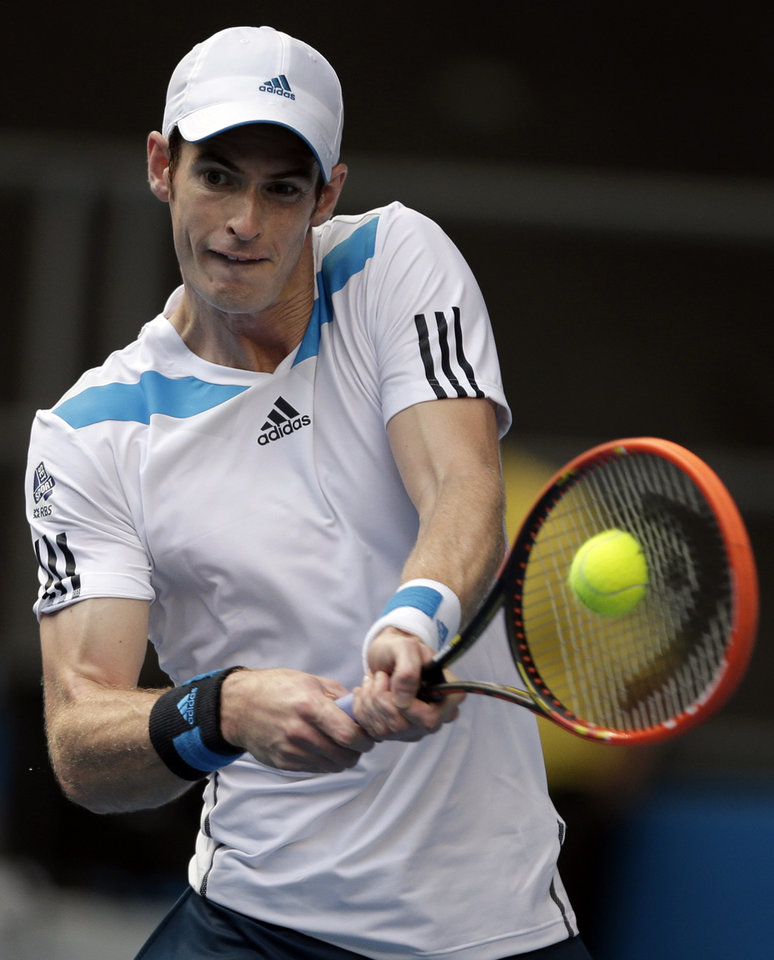 Photo - Andy Murray of Britain makes a backhand return to Stephane Robert of France during their fourth round match at the Australian Open tennis championship in Melbourne, Australia, Monday, Jan. 20, 2014.(AP Photo/Rick Rycroft)