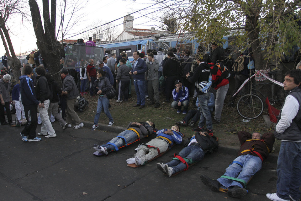 "Train passengers wait to be transported to a hospital after they were injured in a train crash in the outskirts of Buenos Aires, Argentina, Thursday, June 13, 2013. A two-level train slammed into another that had stopped between stations during the morning commute Thursday. Firefighters and police are pulling passengers from the wreckage. Train operator spokesman Pablo Gunning says there are ""various fatalities"" though has not specified how many. (AP Photo)"