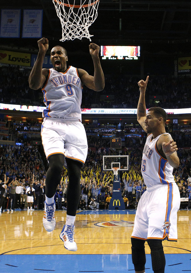 Photo - Oklahoma City's Serge Ibaka (9) and Thabo Sefolosha (25) celebrate Russell Westbrook's game-winning three pointer in the overtime of the NBA game between the Oklahoma City Thunder and the Golden State Warriors at the Chesapeake Energy Arena, Friday, Nov. 29, 2013. Photo by Sarah Phipps, The Oklahoman