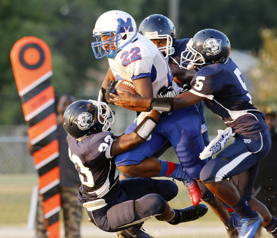 Photo - Milwood's Andre Clanton (22) is brought down after picking up a first down by several SS players  during the high school football game between Millwood and Star Spencer in Spencer, Thursday, September 5, 2013. Photo by Doug Hoke, The Oklahoman