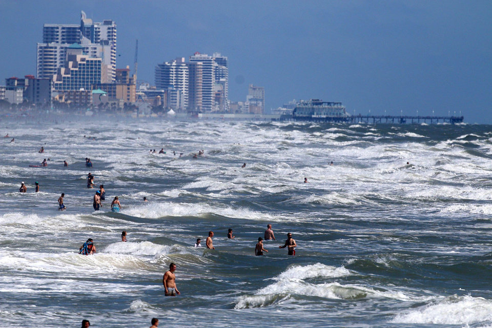 Photo - People deal with the high surf and currents off Daytona Beach generated by Tropical Storm Arthur on Tuesday, July 1, 2014.  A tropical storm watch was in effect for a swath of Florida's east coast. The National Hurricane Center urged those as far north as parts of Virginia to monitor Tropical Storm Arthur's path. (AP Photo/The Daytona Beach News-Journal, Jim Tiller)