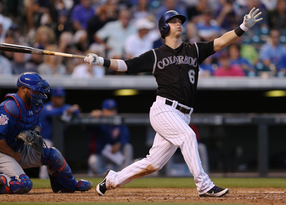 Photo - Colorado Rockies' Corey Dickerson, right, swings at a pitch as Chicago Cubs catcher Wellington Castillo fields the ball in the fourth inning of a baseball game in Denver on Wednesday, Aug. 6, 2014. Dickerson went on to hit an RBI-triple in the appearance at the plate. (AP Photo/David Zalubowski)