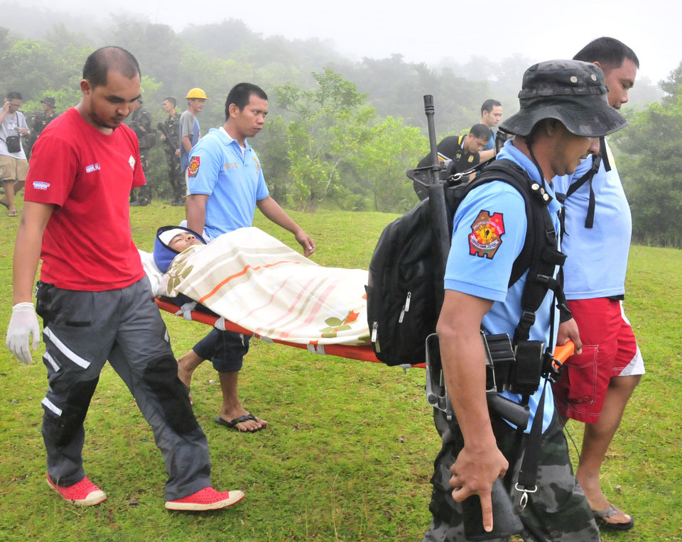 Photo - Police and rescuers carry Nicas Mabao Jr. to a waiting ambulance after surviving a steam-driven explosion of Mayon volcano, one of the Philippines' most active volcanoes, Tuesday, May 7, 2013 in Albay province about 450 kilometers (285 Miles) southeast of Manila, Philippines. Mayon volcano rumbled to life Tuesday, spewing room-sized rocks toward nearly 30 surprised climbers, killing five and injuring others that had to be fetched with rescue helicopters and rope. (AP Photo/Nelson Salting)
