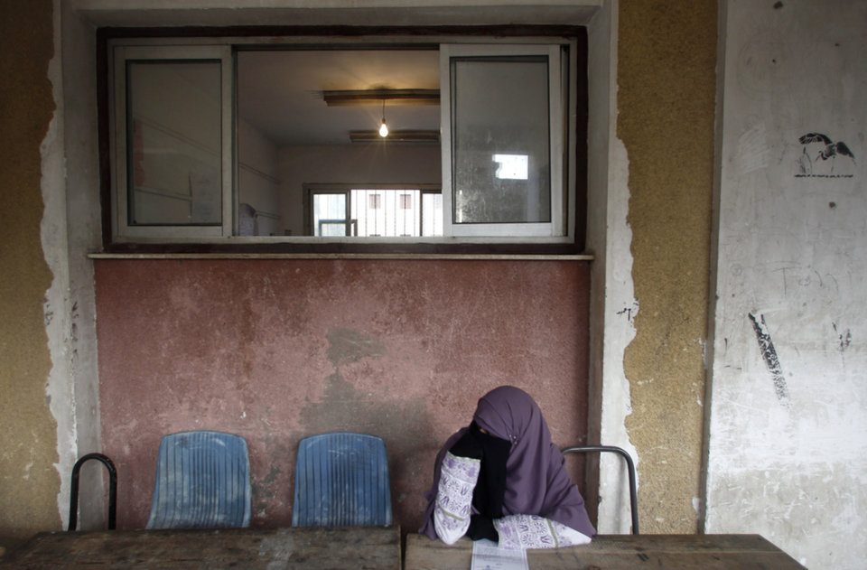 An Egyptian woman sits outside a polling station during a referendum on a disputed constitution drafted by Islamist supporters of President Mohammed Morsi in Cairo, Egypt, Saturday, Dec. 15, 2012. (AP Photo/Petr David Josek)