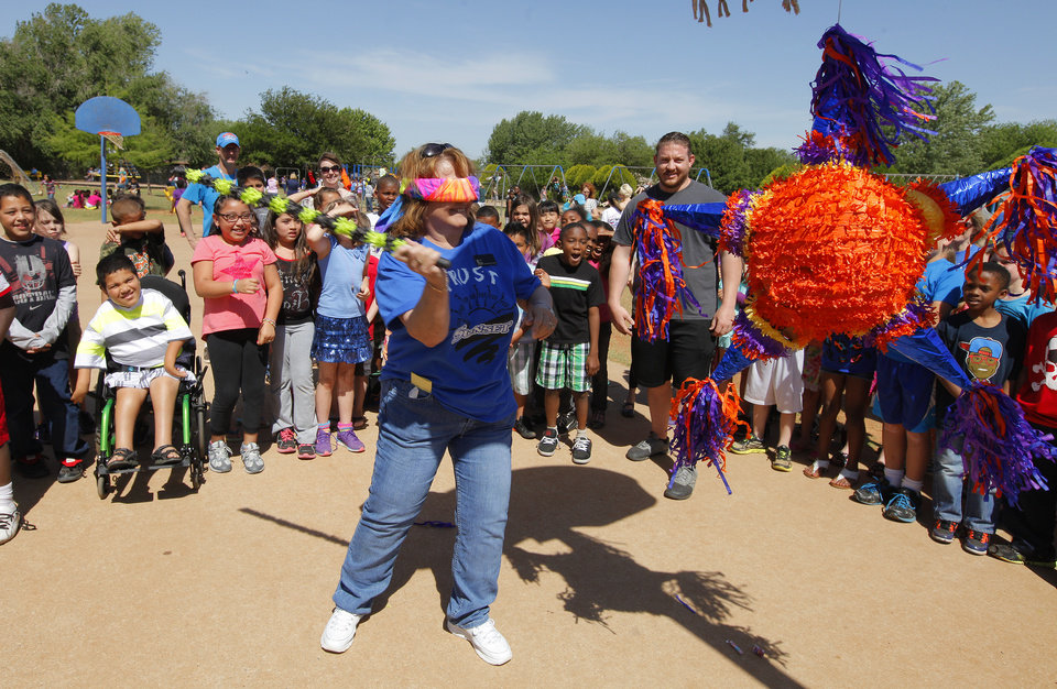 Photo -  Students look on as third-grade teacher Judy Newsom tries to break a pinata filled with candy during a Cinco de Mayo celebration at Sunset Elementary School on Monday. Photo by Paul B. Southerland, The Oklahoman   PAUL B. SOUTHERLAND -