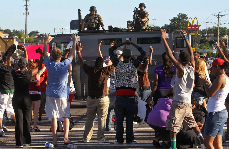 Photo - Protesters raise their hands in front of police atop an armored vehicle in Ferguson, Mo. on Wednesday, Aug. 13, 2014. On Saturday, Aug. 9, 2014, a white police officer fatally shot Michael Brown, an unarmed black teenager, in the St. Louis suburb. (AP Photo/St. Louis Post-Dispatch, J.B. Forbes)