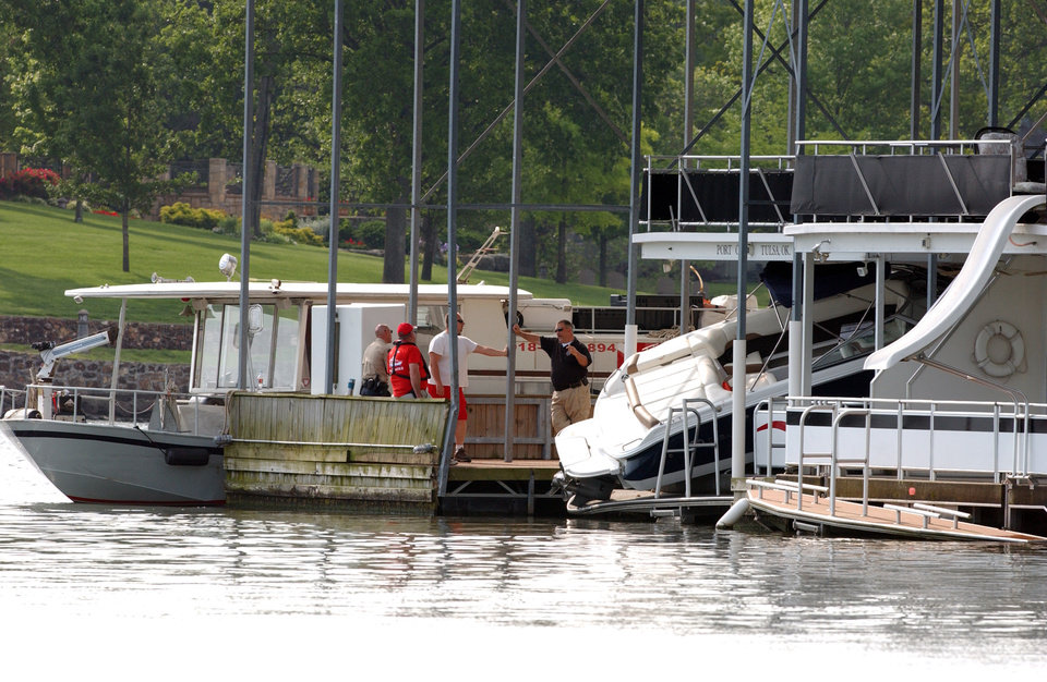 Photo - Officals beside the boat that crashed into a houseboat docked leaving 2 dead at Arrowhead Resort on Grand Lake.  Gary Crow/For the Oklahoman