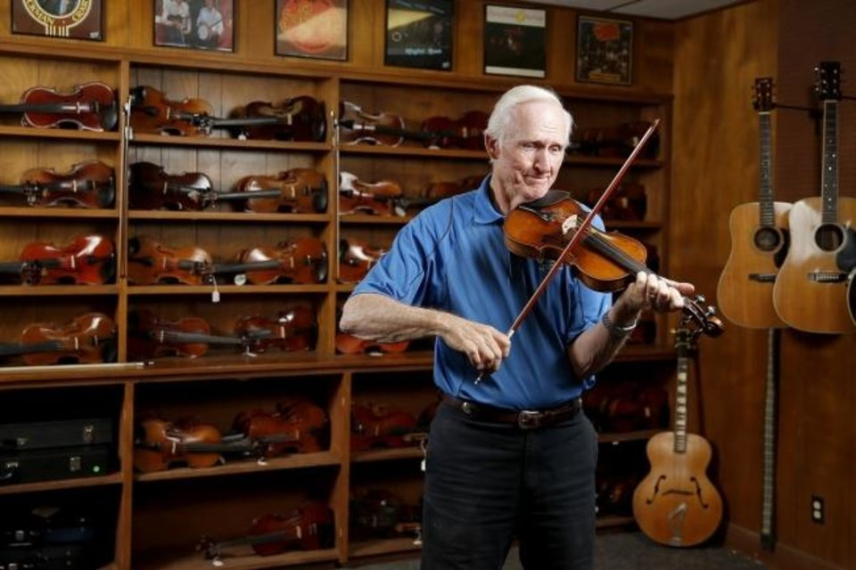 Photo -  Byron Berline plays on July 5, 2019, inside his Double Stop Fiddle Shop in Guthrie.  [Bryan Terry/The Oklahoman Archives]