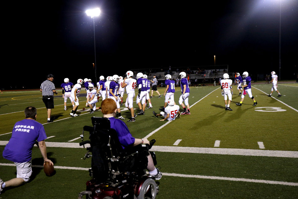 Keegan Erbst watches from the sidelines during a Sequoyah Middle School football team as they huddle up during halftime of their game, Thursday, September 27, 2012. Keegan, who has muscular dystrophy and is confined to a wheelchair, got involved with the team after players Lucas Coker, Colton James, and Parker Tumleson, suggested it to the coach.  Photo by Bryan Terry, The Oklahoman