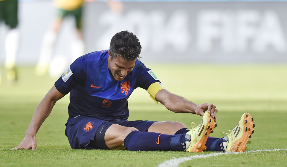 Photo - Netherlands' Robin van Persie stretches during the group B World Cup soccer match between Australia and the Netherlands at the Estadio Beira-Rio in Porto Alegre, Brazil, Wednesday, June 18, 2014.  (AP Photo/Martin Meissner)