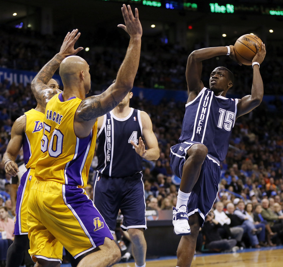 Photo - Oklahoma City's Reggie Jackson (15) shoots against LA's Robert Sacre (50) during an NBA basketball game between the Los Angeles Lakers and the Oklahoma City Thunder at Chesapeake Energy Arena in Oklahoma City, Friday, Dec. 13, 2013. PHOTO BY NATE BILLINGS, The Oklahoman