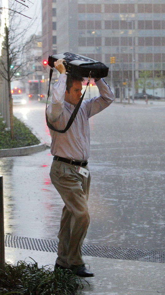 Photo - A pedestrian hurries to work in the pouring rain as thunderstorms move through near Harvey and Park in downtown Oklahoma City on Monday.  PAUL B. SOUTHERLAND - PAUL B. SOUTHERLAND