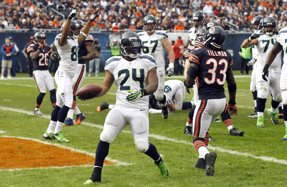 Photo - Seattle Seahawks running back Marshawn Lynch (24) celebrates after rushing for a touchdown against the Chicago Bears in the first half of an NFL football game in Chicago, Sunday, Dec. 2, 2012. Bears' Charles Tillman (33) walks away. (AP Photo/Charles Rex Arbogast)