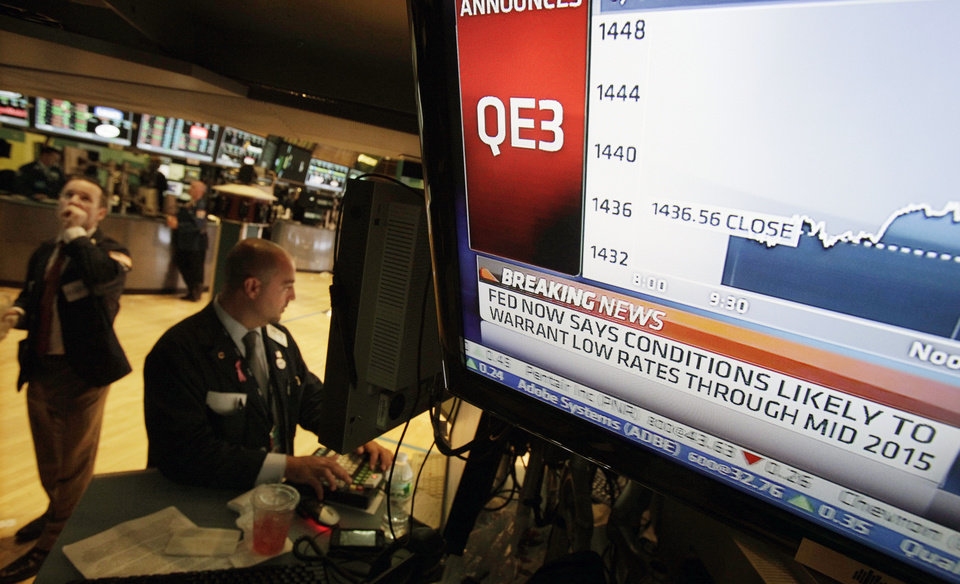 Photo -   Specialist Frank Babino, center, works at his post on the floor of the New York Stock Exchange Thursday, Sept. 13, 2012. The Federal Reserve unleashed a series of aggressive actions Thursday intended to stimulate the still-weak economy by making it cheaper for consumers and businesses to borrow and spend. (AP Photo/Richard Drew)