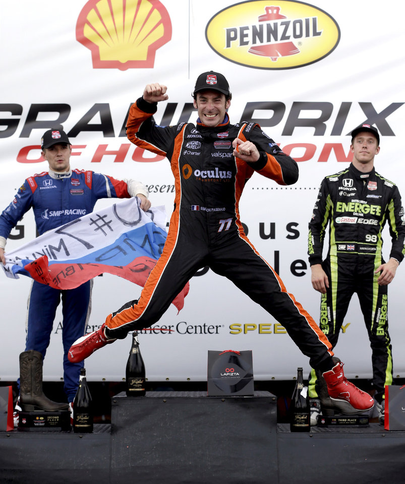 Photo - Simon Pagenaud (77), of France, leaps as he celebrates his victory on the winner's stage after the second IndyCar Grand Prix of Houston auto race Sunday, June 29, 2014, in Houston. Joining him on stage are second place finisher Mikhail Aleshin, left, of Russia, and third place finisher Jack Hawksworth, right, of England. (AP Photo/David J. Phillip)