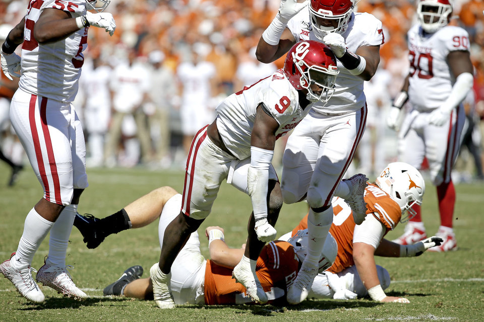 Photo - Oklahoma linebacker Kenneth Murray (9) celebrates with defensive lineman Ronnie Perkins (7) after bringing down Texas quarterback Sam Ehlinger (11)  during the Red River Showdown college football game between the University of Oklahoma Sooners (OU) and the Texas Longhorns (UT) at Cotton Bowl Stadium in Dallas, Saturday, Oct. 12, 2019. Oklahoma won 34-27. [Bryan Terry/The Oklahoman]