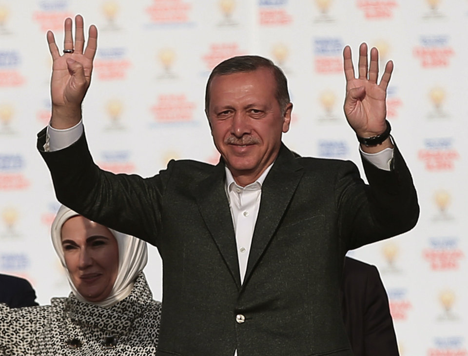 Photo - FILE - In this March 23, 2014 file photo, Turkish Prime Minister Recep Tayyip Erdogan addresses supporters of his Justice and Development Party during a rally in Istanbul, Turkey. Erdogan has been ensnared in a corruption scandal that has toppled four Cabinet ministers. He has provoked outrage at home and abroad with an attempt to block Twitter and YouTube. His incessant us-against-them rhetoric and conspiracy theories have alienated allies. Meanwhile, the Turkish Lira has fallen, interest rates are up and the Turkish economy has fallen off a cliff. It all might be enough to oust any leader. But as Turks prepare to vote in local elections Sunday, it's all about Erdogan. His wife Emine Erdogan is at the left.(AP Photo/Emrah Gurel, File)