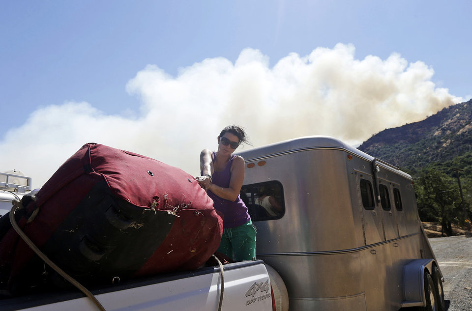 Heather Seeno loads equipment onto a truck at Ranch North Peak as a wildfire approaches on Monday, Sept. 9, 2013, in Clayton, Calif. A wildfire burning outside Mount Diablo State Park has forced dozens of residents and animals to evacuate Monday. (AP Photo/Marcio Jose Sanchez)