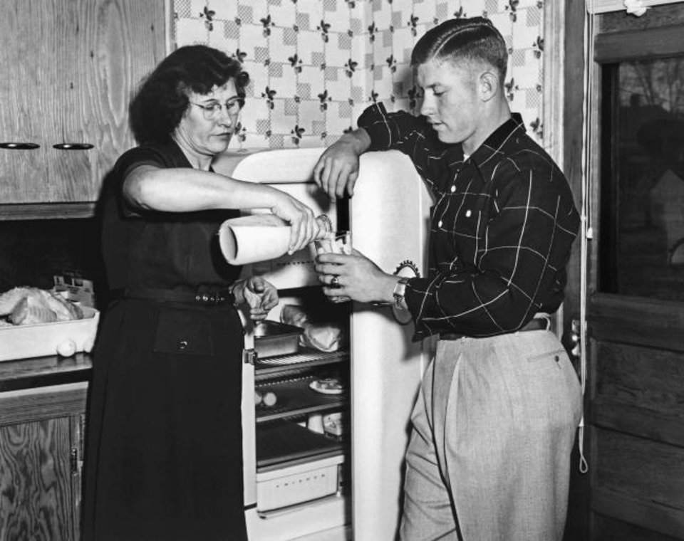 Photo -  Lovell Richardson Mantle pours a glass of milk for her son, Mickey Mantle, at the family's home in Commerce in April 1951. [AP Photo/William P. Straeter]