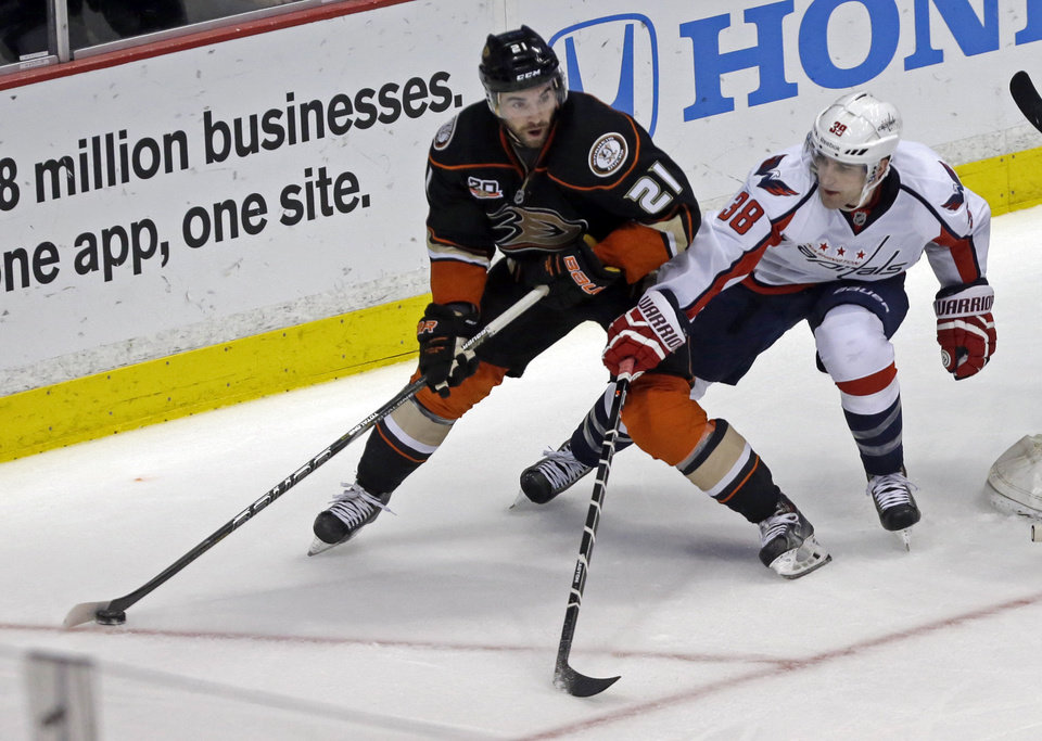Photo - Anaheim Ducks right winger Kyle Palmieri (21) and Washington Capitals defenseman Jack Hillen (38) skate in the second period of an NHL hockey game Tuesday, March 18, 2014, in Anaheim, Calif. (AP Photo/Reed Saxon)