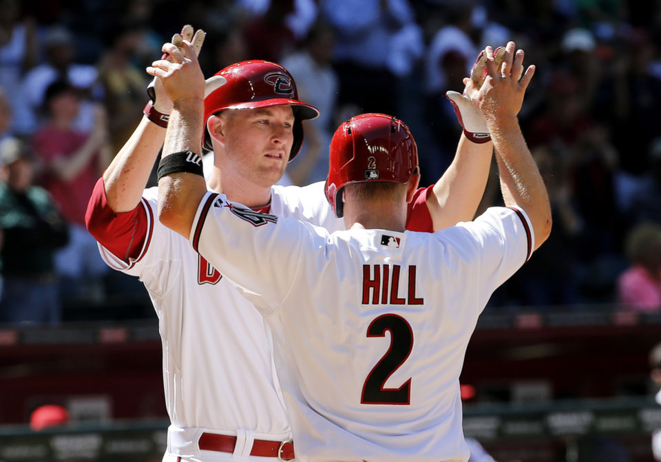Photo - Arizona Diamondbacks' Mark Trumbo, left, high-fives teammate Aaron Hill (2) after hitting a two-run home run against the San Francisco Giants during the sixth inning of a baseball game on Thursday, April 3, 2014, in Phoenix. (AP Photo/Matt York)