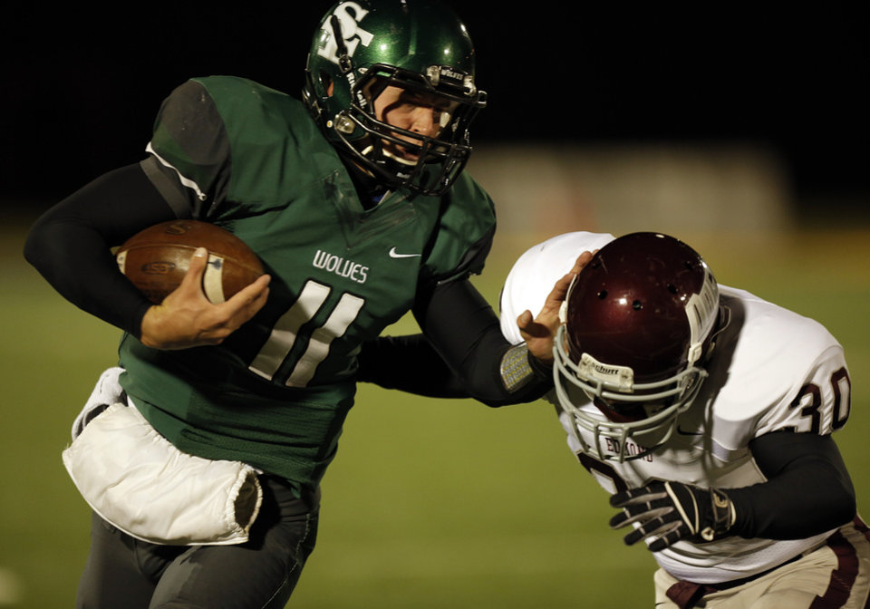 Santa Fe's Justice Hansen (11) blocks Memorial's Colin Simpson (30) while he runs the ball during a high school football game between Edmond Memorial and Edmond Santa Fe at Wantland Stadium in Edmond, Okla., Friday, Oct. 26, 2012.  Photo by Garett Fisbeck, The Oklahoman